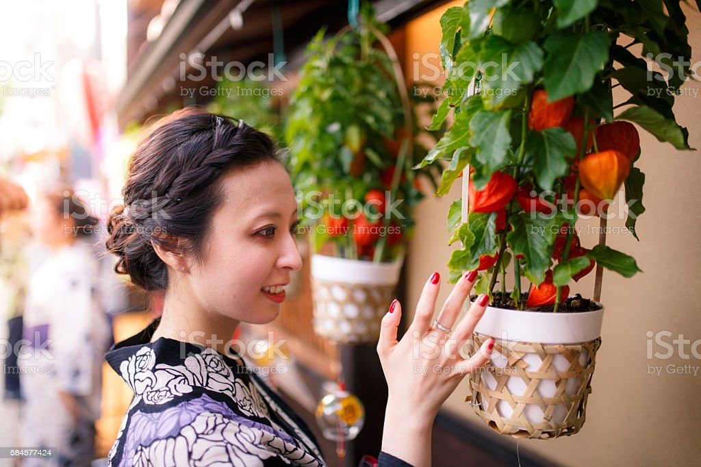 Japanese woman touching houzuki ground cherry stock photo