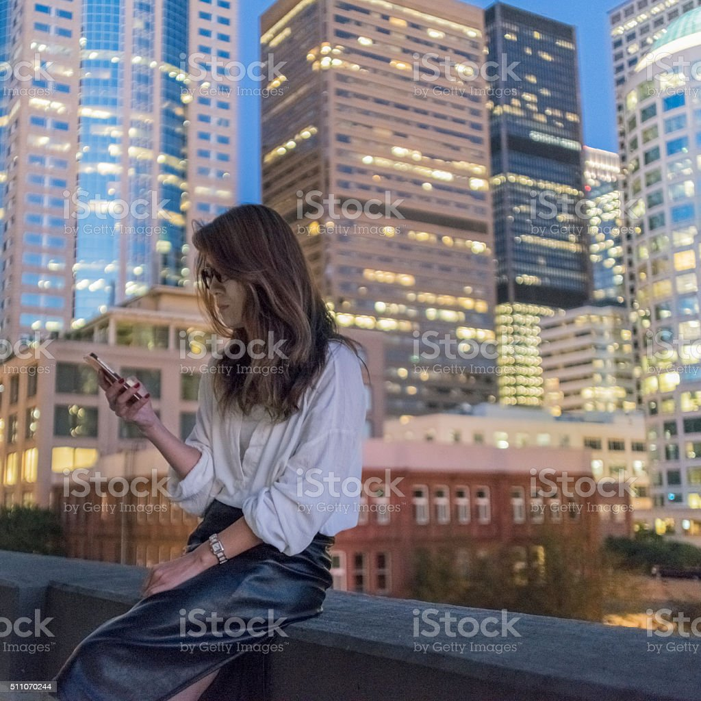 Japanese woman using cellphone at night stock photo