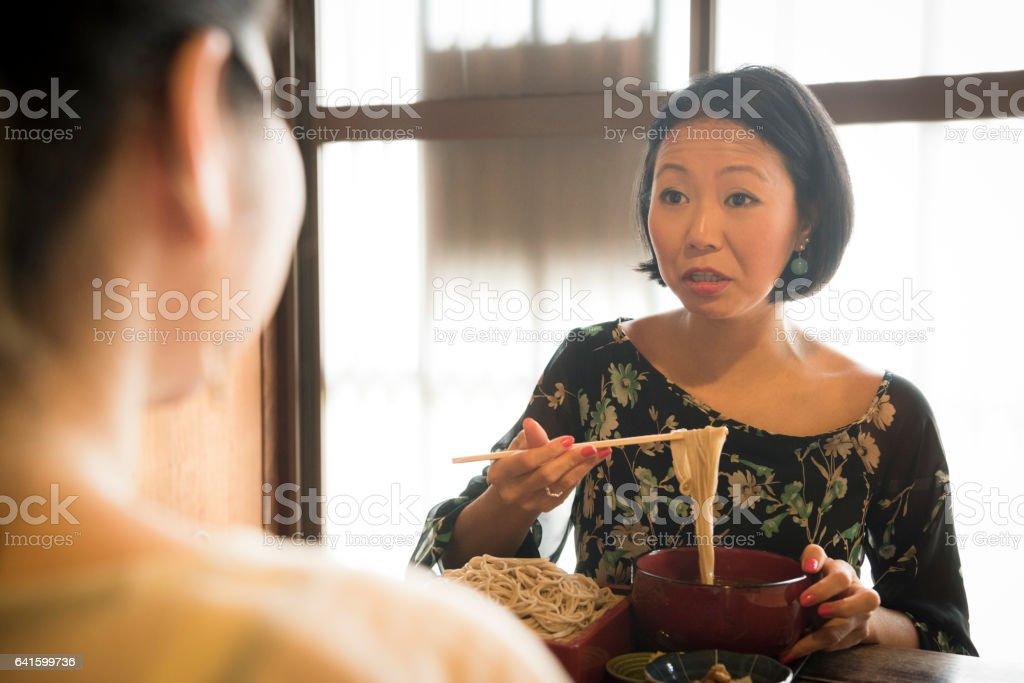 Japanese woman using chopsticks at soba noodle restaurant stock photo
