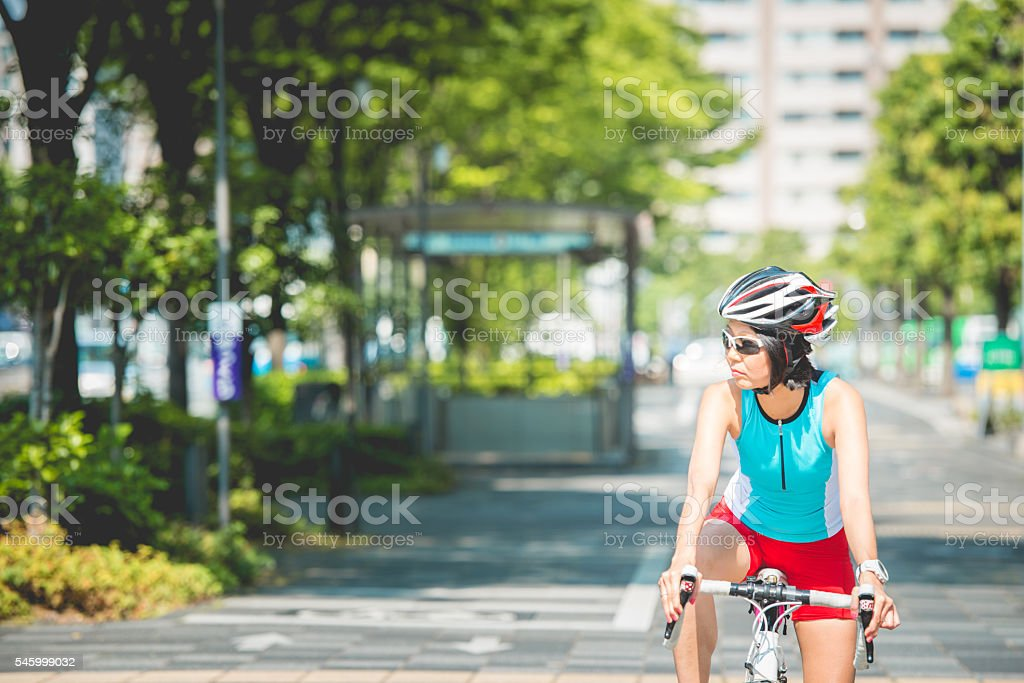 Japanese Woman Waiting while Riding Bike in Kyoto City, Japan stock photo