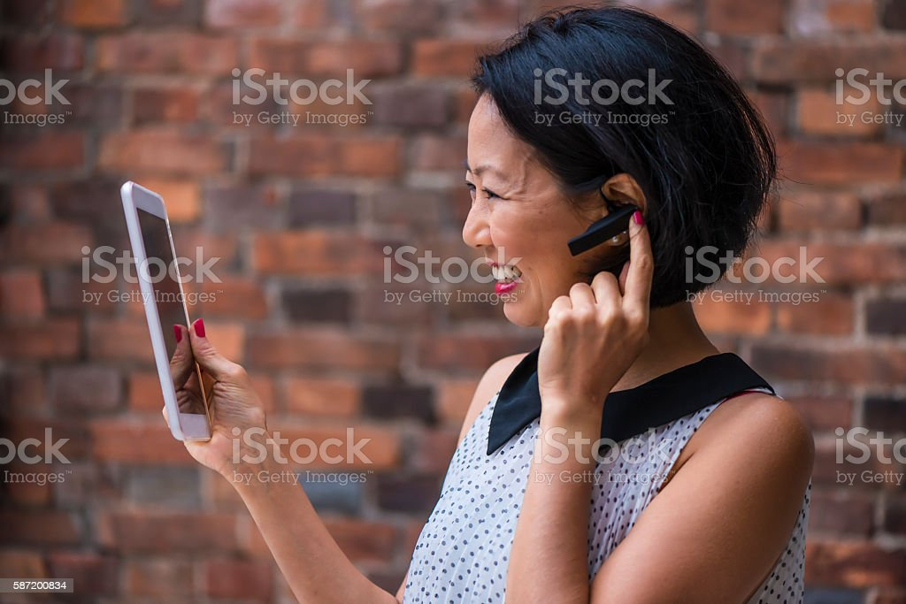 Japanese woman with bluetooth talking stock photo