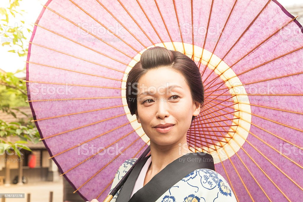 Japanese woman with paper umbrella under the sun stock photo