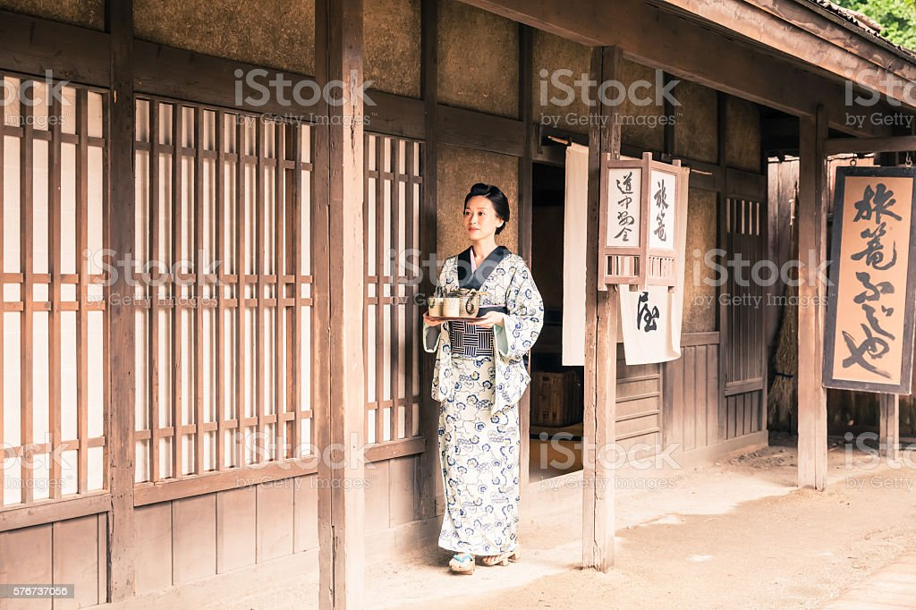 Japanese woman with tea tray outside a traditional japanese house stock photo