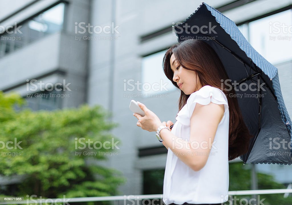 Japanese woman with umbrella using phone stock photo