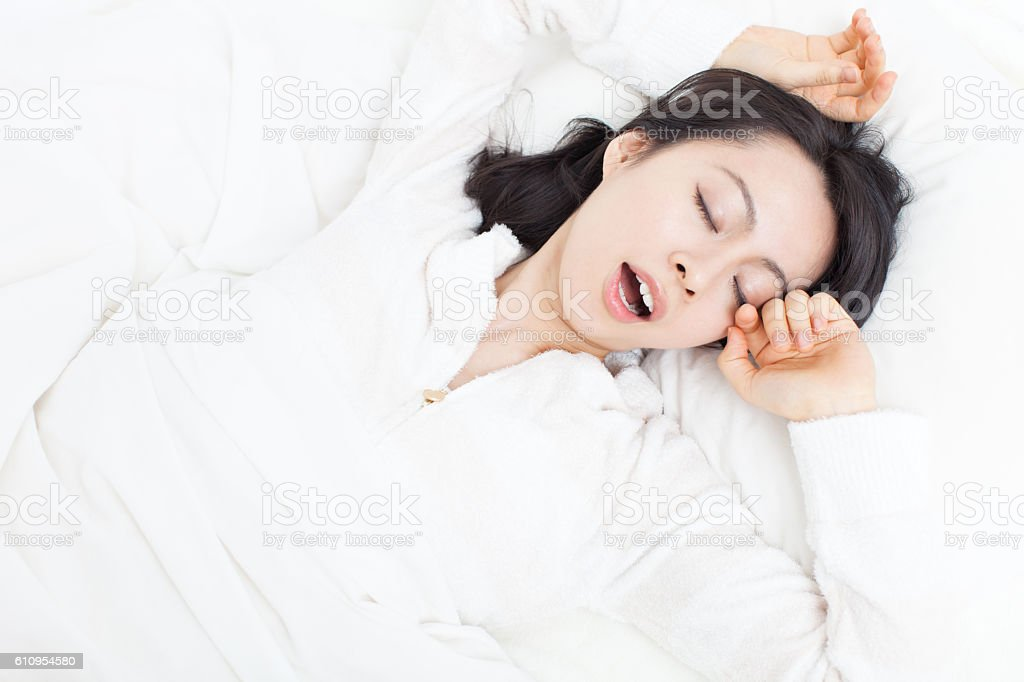 Japanese woman yawning in the bed stock photo