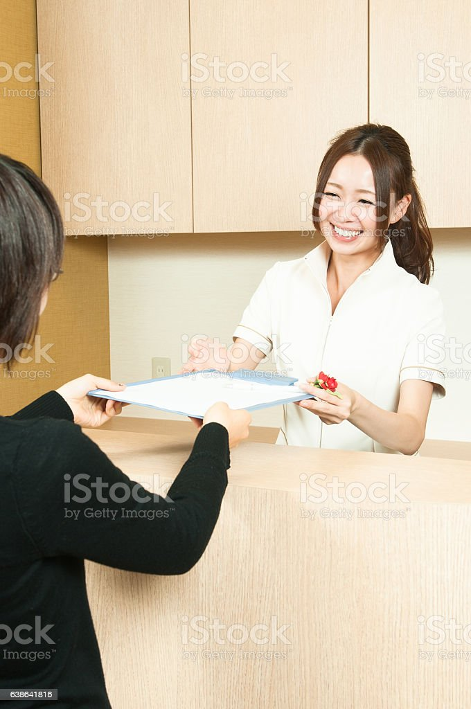 Japanese women at the reception hand over the questionnaire stock photo