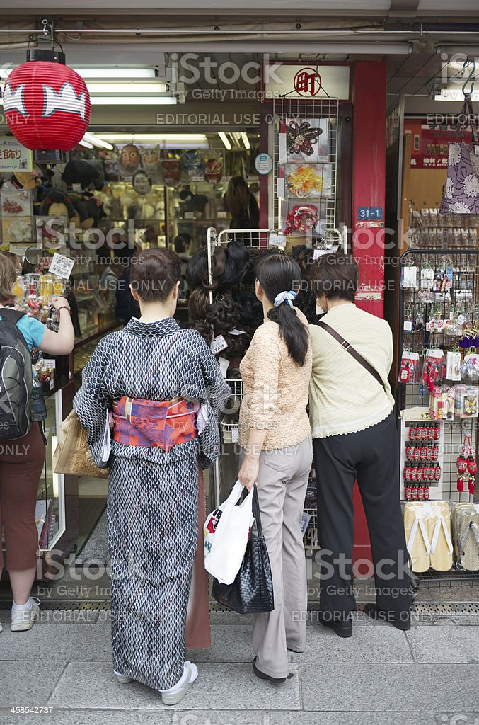 Japanese women looking at wigs in Tokyo market royalty-free stock photo