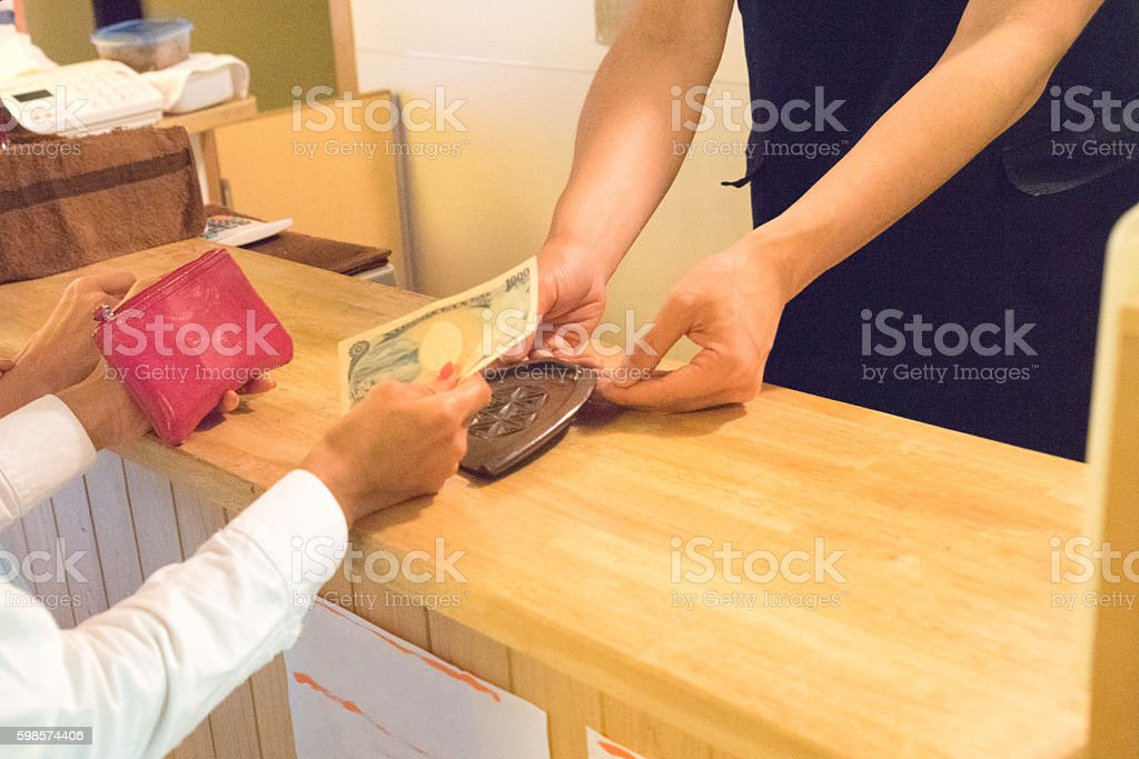 Japanese women making payment with cash in a cafe stock photo