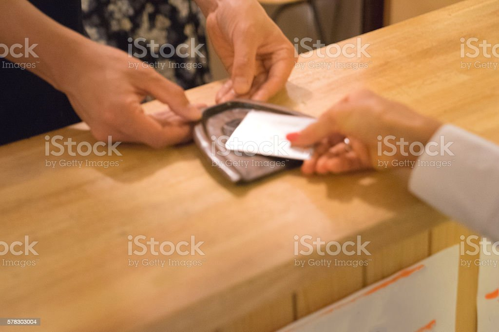 Japanese women making payment with credit card in a cafe stock photo