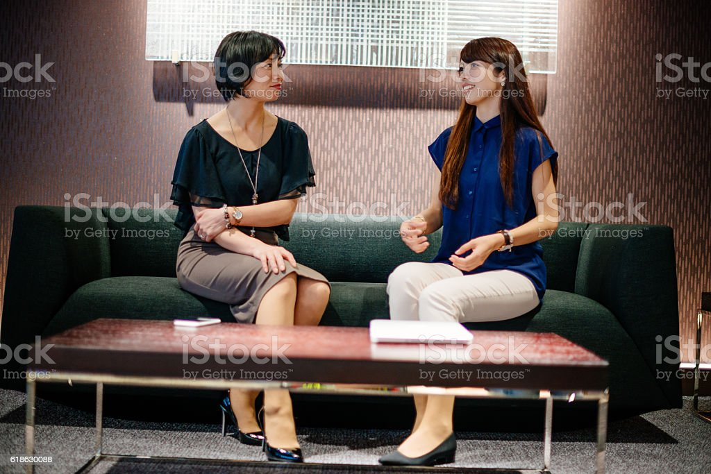 Japanese women sitting on couch and chatting stock photo