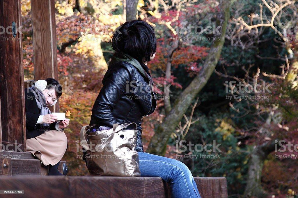 Japanese women taking photo at Tofuku-ji Temple, Kyoto in Autumn stock photo