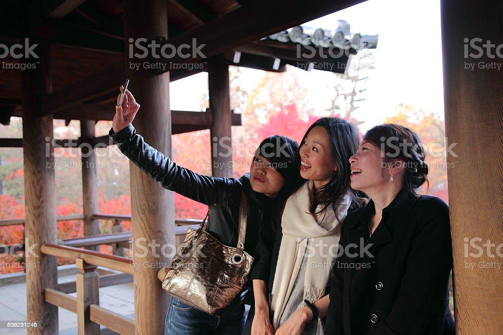 Japanese women taking selfie on bridge at Tofuku-ji Temple, Kyoto stock photo