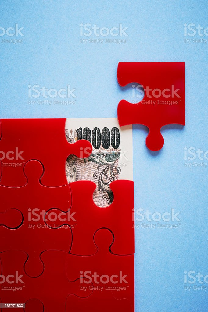 Japanese yen bill and jigsaw puzzle stock photo