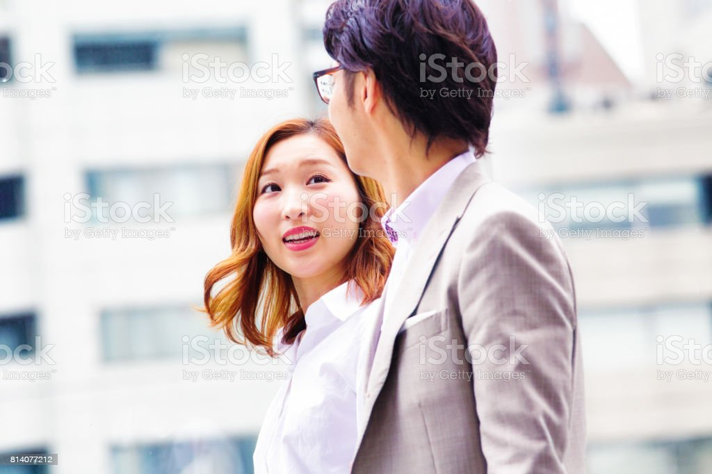 Japanese young female worker inspired by male colleague stock photo