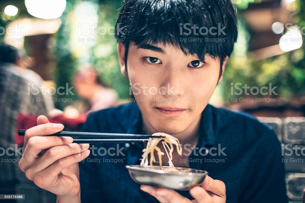 Japanese young man eating vegetables stock photo