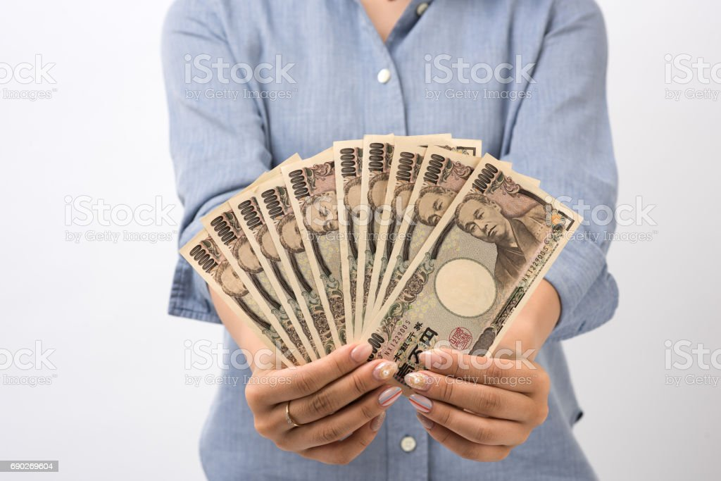 A Japanese young woman counting ten thousand yen stock photo
