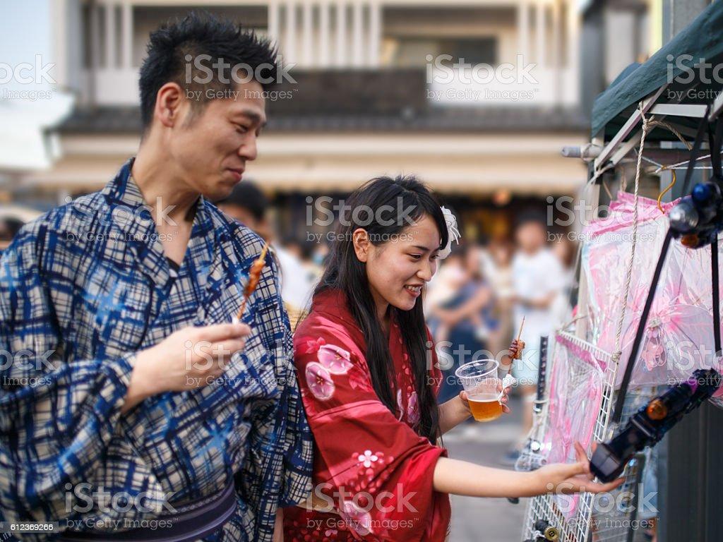 Japanese yukata couple trying out toy gun at festival stock photo