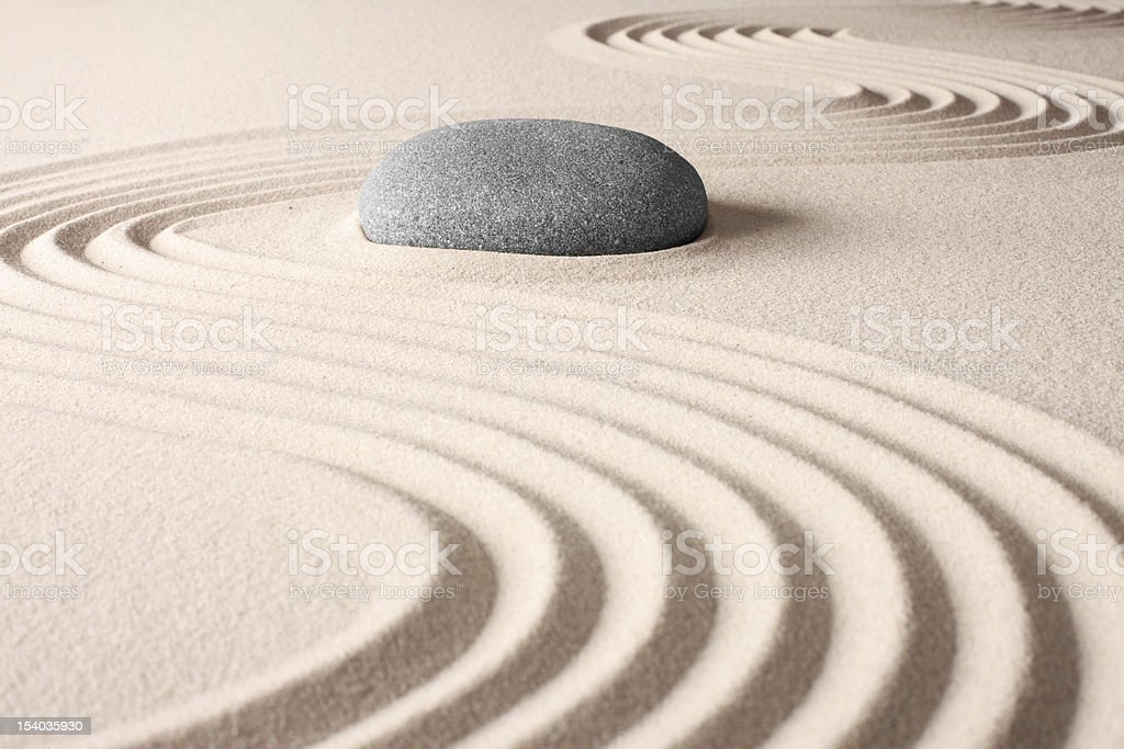 A Japanese zen garden with lines in sand and a gray rock stock photo