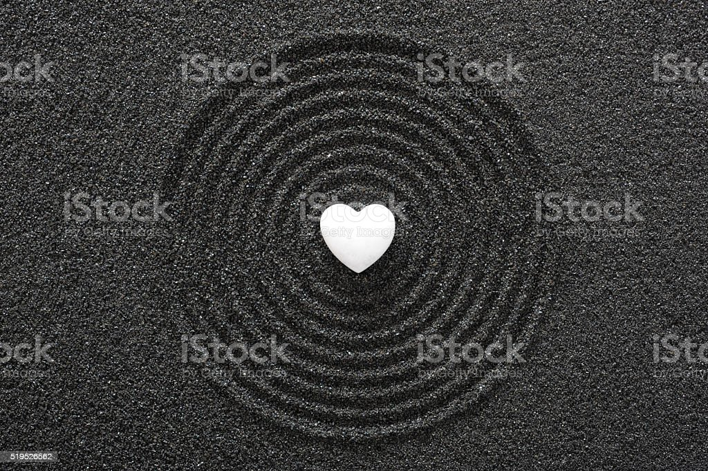 Japanese ZEN garden with white heart in raked sand stock photo