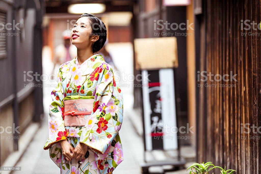 Japenese Girl in Kimono admiring local architecture stock photo