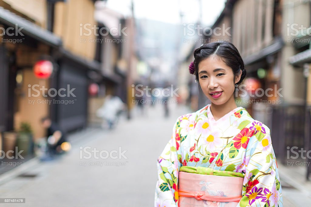 Japenese Girl in Kimono walking along the streets of Kyoto stock photo