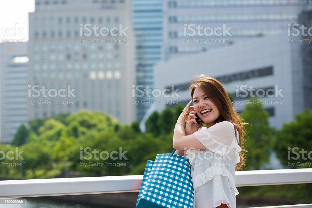 Japnese woman with shopping bags and a smart phone stock photo