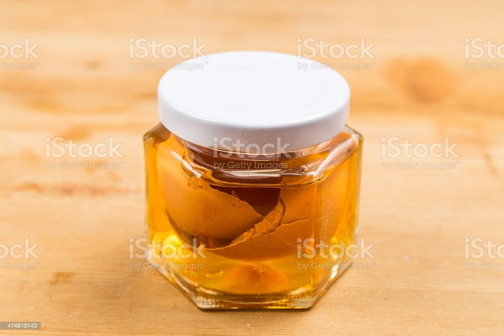 Jar containing soaked egg shell in apple cider vinegar stock photo