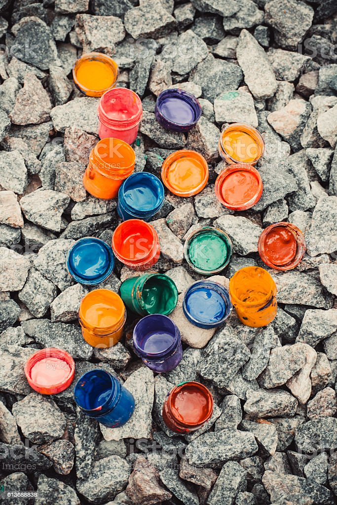 jar from under the paint of different colors on rocks stock photo