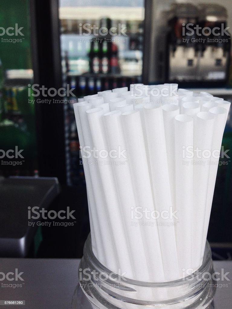 Jar full of plastic straws on a bar counter stock photo