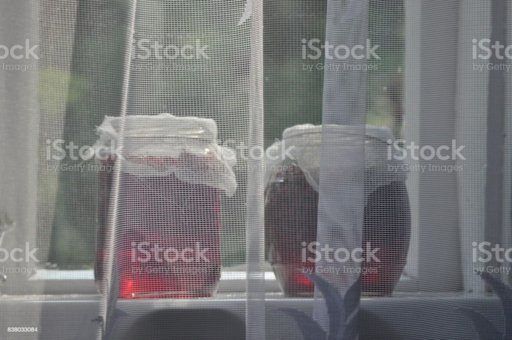 Jar, jars of jam with red currants standing on the windowsill in the farmhouse. View of the garden. stock photo
