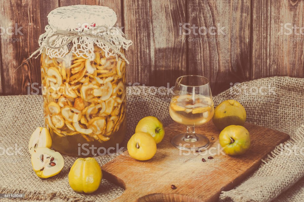 Jar of alcoholic tincture and glass of drink with quince fruits on a jute background. stock photo