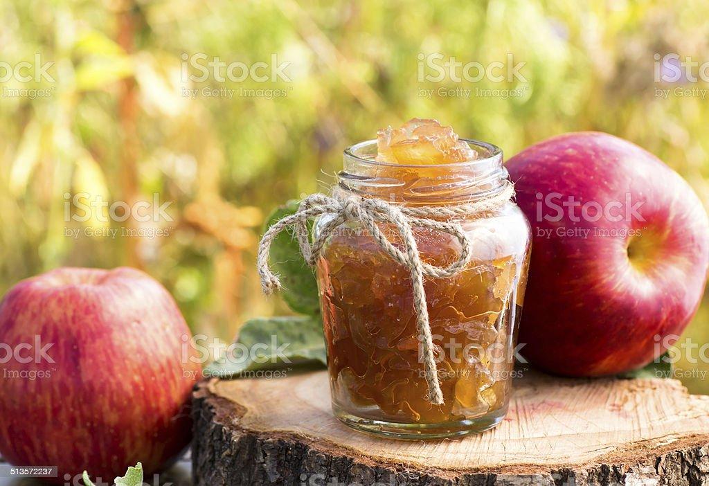 Jar of apple preserves on grass background stock photo