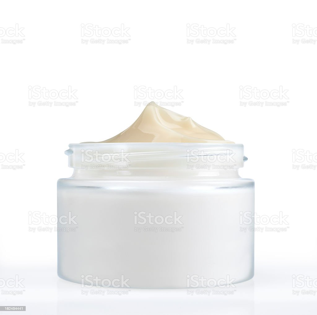 Jar of beige colored face cream upright with the lid off royalty-free stock photo