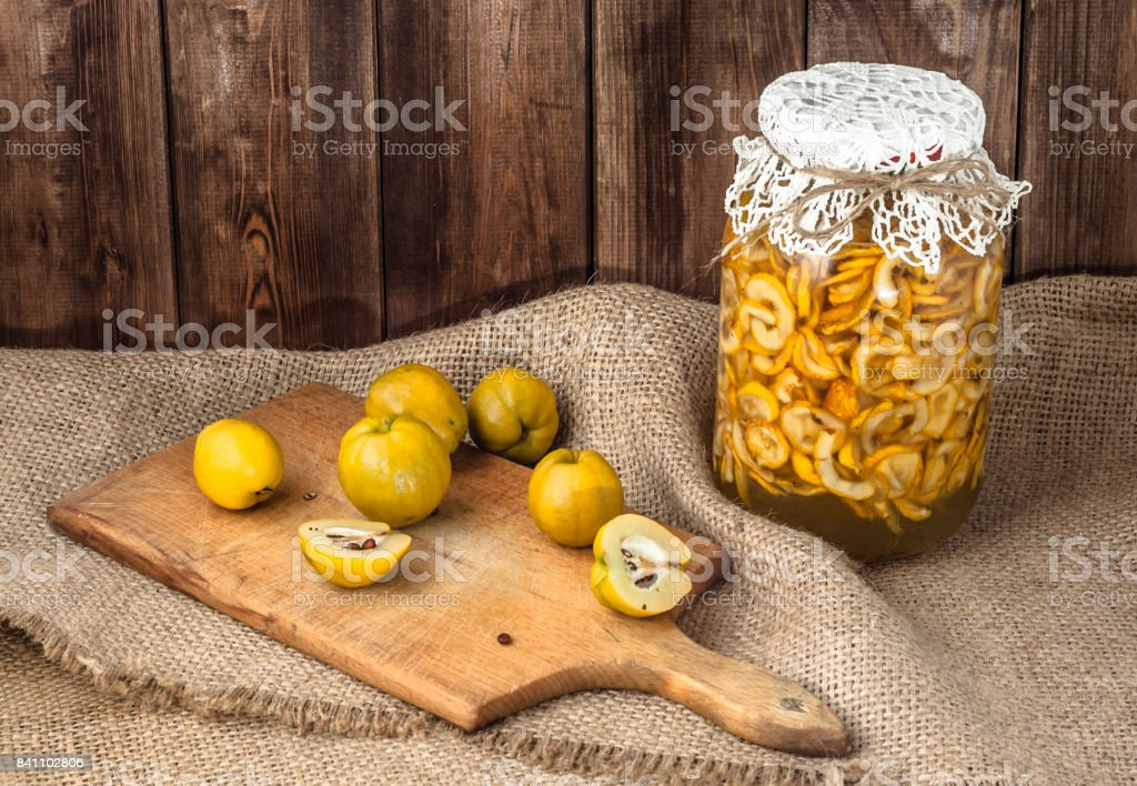 Jar of beverage with quince fruits on a wooden table covered with sackcloth. stock photo