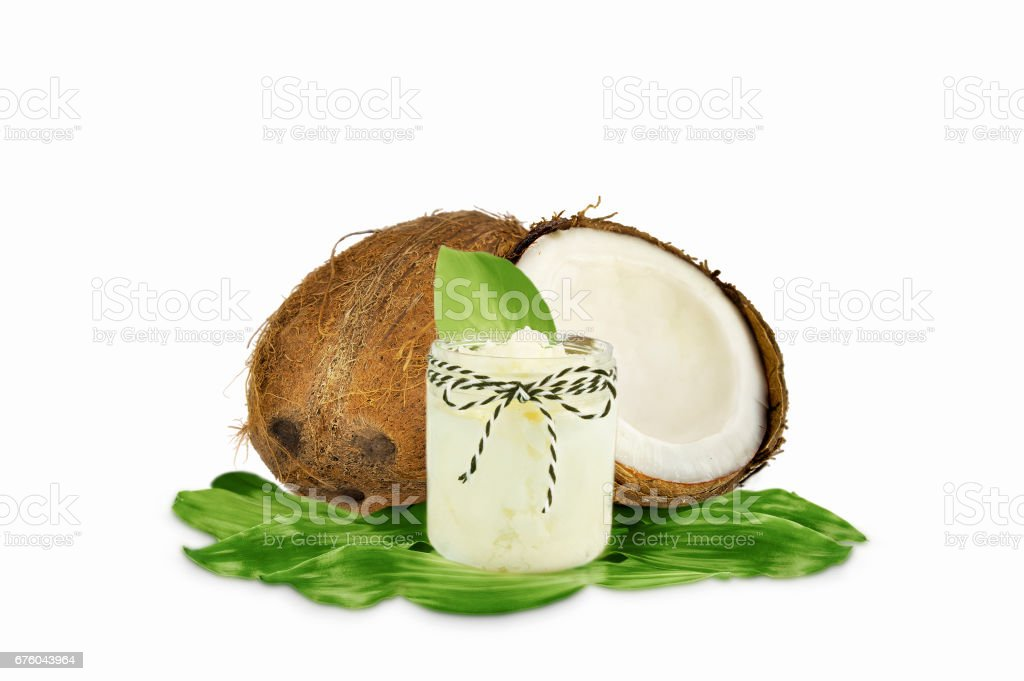 Jar of coconut oil and fresh coconuts isolated on white stock photo