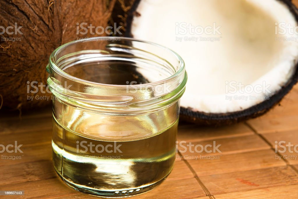 Jar of coconut oil with coconuts on bamboo mat royalty-free stock photo