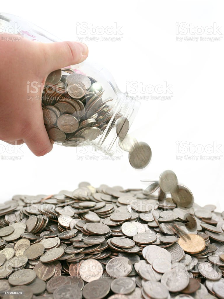 Jar of Coins Falling into a Pile of Change stock photo