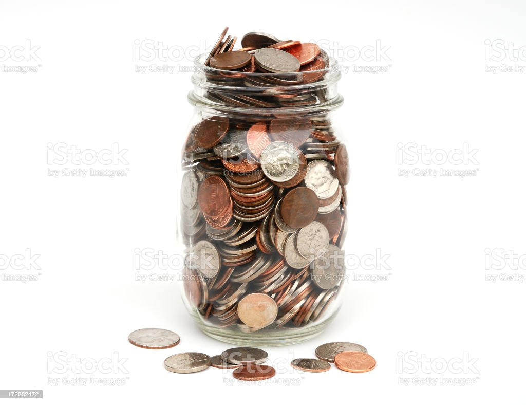 Jar of coins full and overflowing stock photo