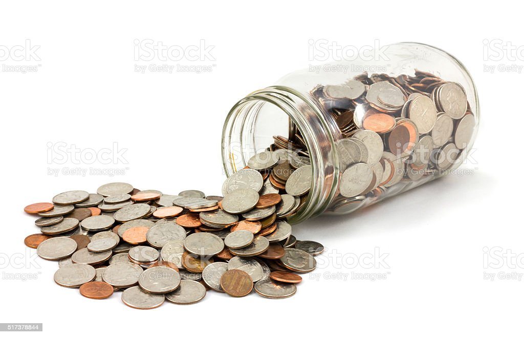 Jar of Coins Spilled on White Background stock photo