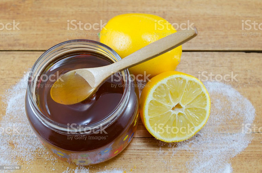 Jar of dark honey a wooden spoon and lemons royalty-free stock photo