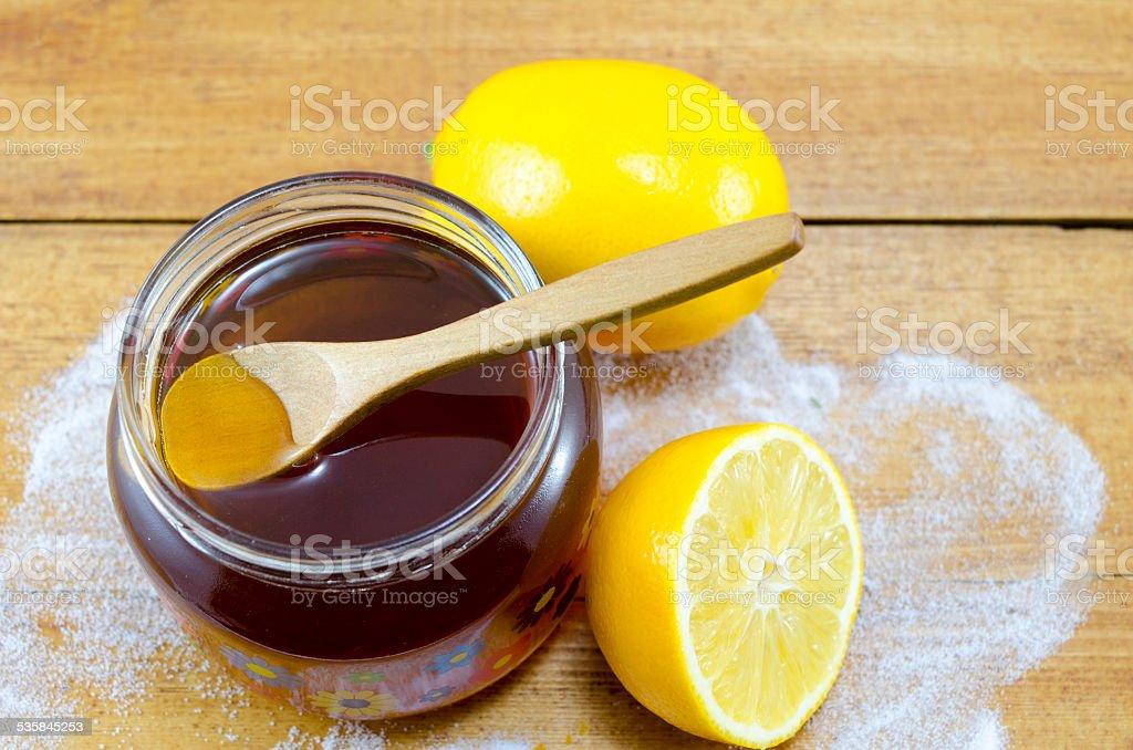 Jar of dark honey a wooden spoon and lemons royalty-free stock photo