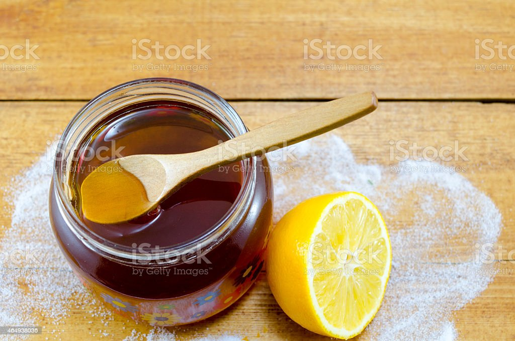 Jar of dark honey and wooden spoon royalty-free stock photo