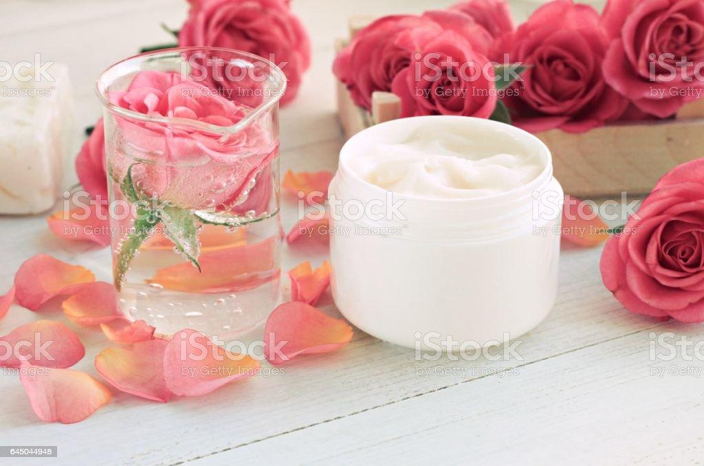 Jar of facial rose anti-age toner and cream, petals stock photo