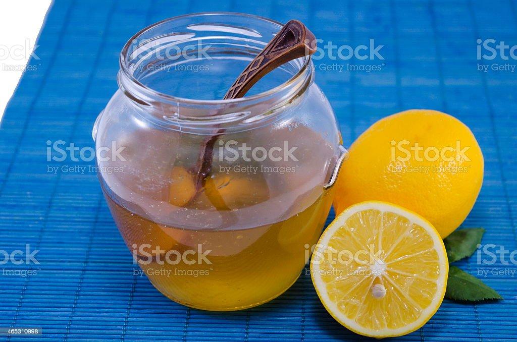 Jar of honey and lemons on blue background royalty-free stock photo