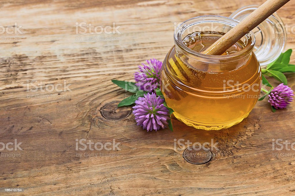 A jar of honey by some flowers on a wooden surface stock photo