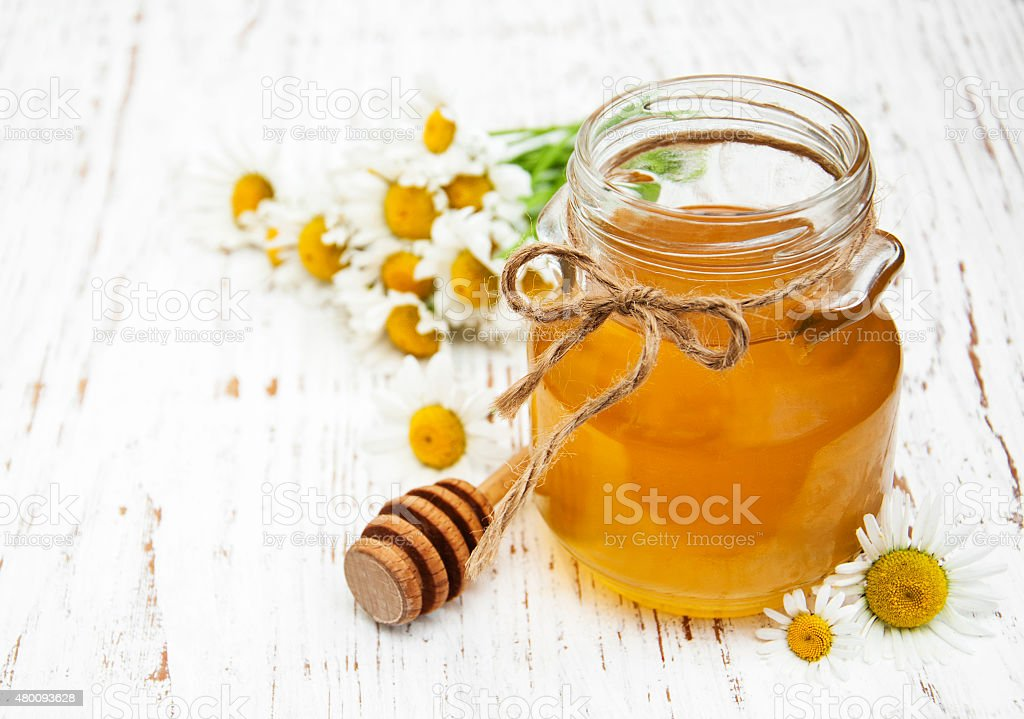 Jar of honey with camomile stock photo
