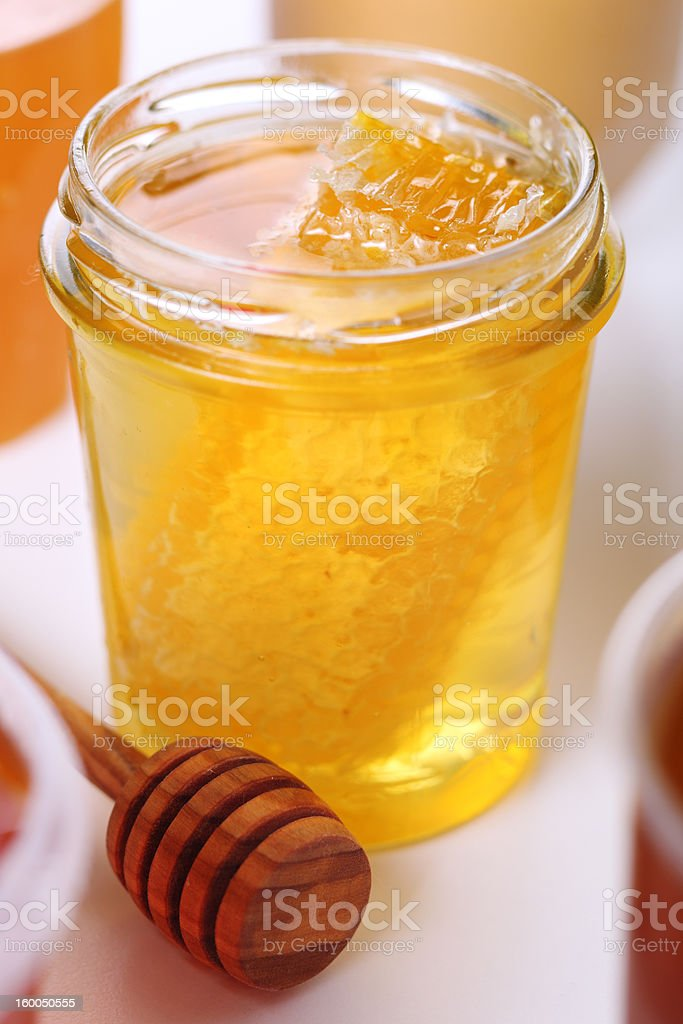 Jar of honey with honeycomb and wooden stick stock photo