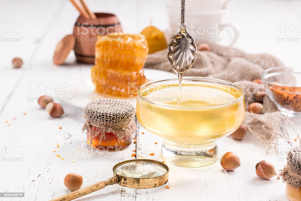 jar of honey with honeycomb on wooden table stock photo
