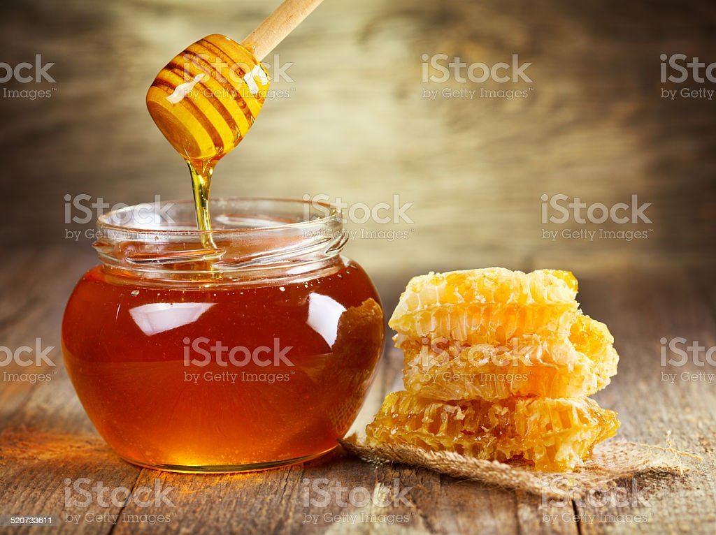 jar of honey with honeycomb stock photo
