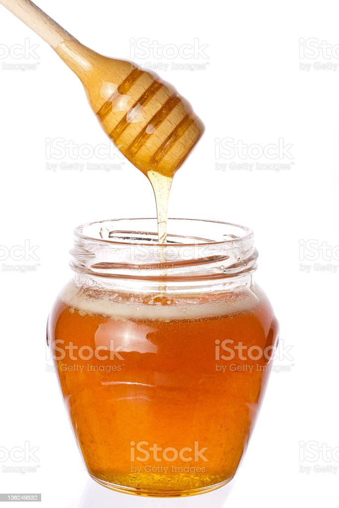 Jar of honey with wooden drizzler royalty-free stock photo